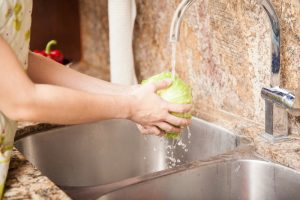 Closeup of the hands of a woman washing a lettuce and some other vegetables in the kitchen sink