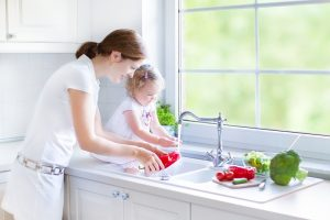 Young beautiful mother and her cute curly toddler daughter washing vegetables together in a kitchen sink getting ready to cook salad for lunch in a sunny white kitchen with a big garden view window