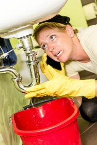 woman under sink with worried expression on her face